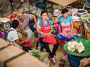 "11 AUGUST 2016 - BANGKOK, THAILAND: Produce sellers relax in Pak Khlong Talat in Bangkok. Pak Khlong Talat (literally ""the market at the mouth of the canal"") is the best known flower market in Thailand. It is the largest flower market in Bangkok. Most of the shop owners in the market sell wholesale to florist shops in Bangkok or to vendors who sell flower garlands, lotus buds and other floral supplies at the entrances to temples throughout Bangkok. There is also a fruit and produce market which specializes in fresh vegetables and fruit on the site. It is one of Bangkok's busiest markets and has become a popular tourist attraction.          PHOTO BY JACK KURTZ"