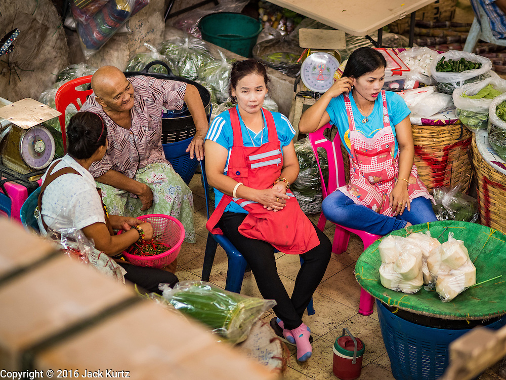 """11 AUGUST 2016 - BANGKOK, THAILAND: Produce sellers relax in Pak Khlong Talat in Bangkok. Pak Khlong Talat (literally """"the market at the mouth of the canal"""") is the best known flower market in Thailand. It is the largest flower market in Bangkok. Most of the shop owners in the market sell wholesale to florist shops in Bangkok or to vendors who sell flower garlands, lotus buds and other floral supplies at the entrances to temples throughout Bangkok. There is also a fruit and produce market which specializes in fresh vegetables and fruit on the site. It is one of Bangkok's busiest markets and has become a popular tourist attraction.          PHOTO BY JACK KURTZ"""
