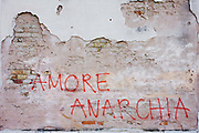 'Love Anarchy' graffiti on a wall on a wall on the Rio de San Margherita canal in Dorsoduro, a district of Venice, Italy. The writing is on bare plaster behind which we see brick of unknown date or era. Anarchist ideology can be seen in various locations around Venice though more common in the more residential district like Dorsoduro and Castello.