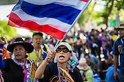 12 MAY 2014 - BANGKOK, THAILAND: A PDRC protestor waves a Thai flag in front of the Parliament. Several thousand protestors with the People's Democratic Reform Committee (PDRC) blocked access to the Thai Parliament building in Bangkok as a part of their continuing anti-government protests. The Parliament is not currently in session and was dissolved by former Prime Minister Yingluck Shinawatra but the Senate is in session. The protestors are demanding that the Senate dissolve the current Pheu Thai caretaker government and appoint a new Prime Minister and cabinet. Members of the Senate leadership met with Suthep Thaugsuban Monday to discuss the impasse.   PHOTO BY JACK KURTZ