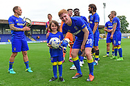 The mascot is presented with the match ball by AFC Wimbledon Midfielder Alfie Egan (28) after the Pre-Season Friendly match between AFC Wimbledon and Watford at the Cherry Red Records Stadium, Kingston, England on 15 July 2017. Photo by Jon Bromley.