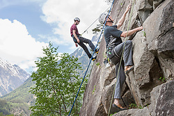 Two male rock climbers scaling a rock face at Oberried climbing garden, Otztal, Tyrol, Austria