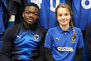 AFC Wimbledon defender Deji Oshilaja (4) and mascot during the EFL Sky Bet League 1 match between AFC Wimbledon and Southend United at the Cherry Red Records Stadium, Kingston, England on 24 November 2018.