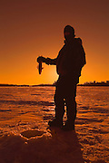 Ice fishing on Lake of teh Woods at sunset<br /> Kenora<br /> Ontario<br /> Canada