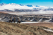 Three Kazakh eagle hunters hunting in the mountains with their golden eagles on horseback, Altai Mountains, Bayan Ulgii, Mongolia