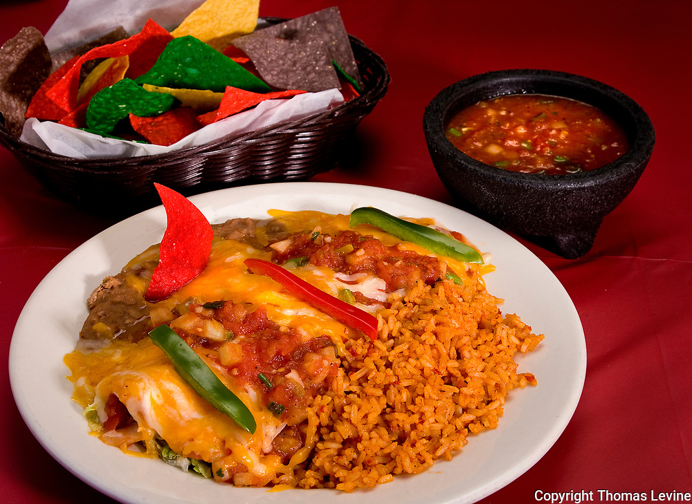 Mexican food cheese enchiladas with rice and beans. Colored Tortilla chips in a basket with salsa dip. RAW to Jpg