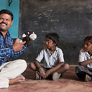 CAPTION: Thanks to The Teacher Foundation (TTF), Prabhuswamy has been trained to lead Quality Circle Time (QCT) sessions in his primary school classrooms. This technique helps him to involve children with special needs in different activities to a much greater extent, as in this instance where he uses a hand puppet to talk to Gowrishankar, who has speech and hearing difficulties. LOCATION: Bedrapura (village), Kasaba (hobli), Chamrajnagar (district), Karnataka (state), India. INDIVIDUAL(S) PHOTOGRAPHED: From left to right: Prabhuswamy, Gowrishankar and Abhi K.