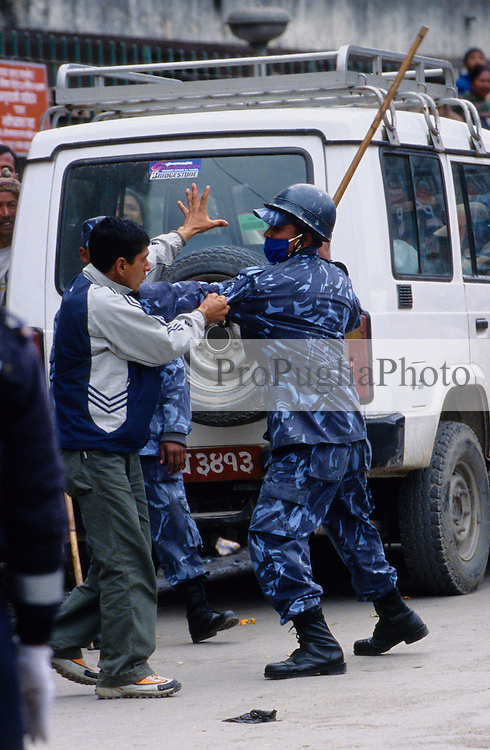 Kathmandu, 18 February 2005. A policeman is blocking a young man from walking freely during the nation's Democracy Day. Authorities have, once again, cut off local telephone lines; public transport has also been banned for most of the day. According to Mr Tara Nath Dahal, president of the Federation of Nepalese Journalists (FNJ), 17.000 security forces are operating in the Kathmandu Valley