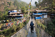 Trekking guide Bibek Gurung walks across a metal suspension footbridge at the hillside village of Tikhedhunga along the Annapurna Sanctuary Trek, Himalaya Mountains, Nepal.