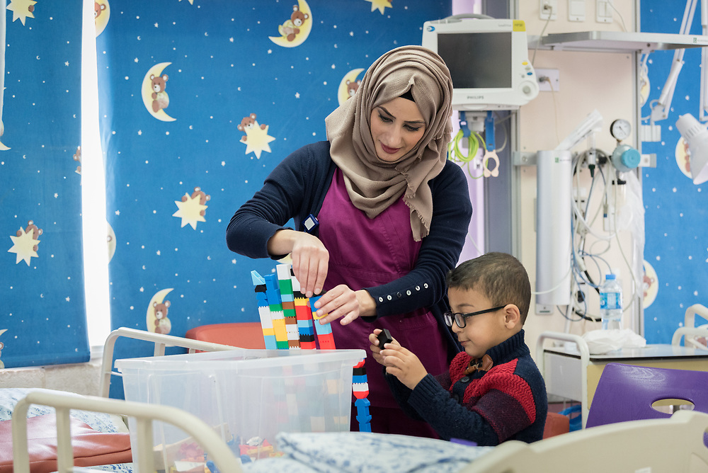 24 February 2020, Jerusalem: Palestinian child Murad is five years old. At the age of one, he was diagnosed and treated for Hepatoblastoma, a rare malignant liver cancer occurring in infants and children. Today, he is at the Augusta Victoria Hospital in Jerusalem for a CT Scan and follow up. Here, playing with Sarah Faroun from Bethany, one of the hospital nurses.