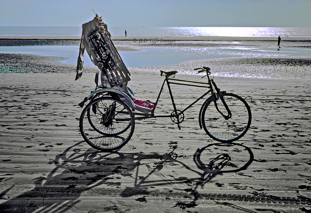 Traditional bicycle rickshaw on the beach at Cox's Bazaar, Bangladesh.  Its owner has left his red sneakers on it.  Two distant figures wade in the distance.  Late day shadows cast on the sand.
