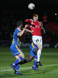 Shrewsbury Town's Luke Waterfall (left) and Salford City's Rory Gaffney battle for the ball during the Emirates FA Cup, first round replay match at the Peninsula Stadium, Salford.