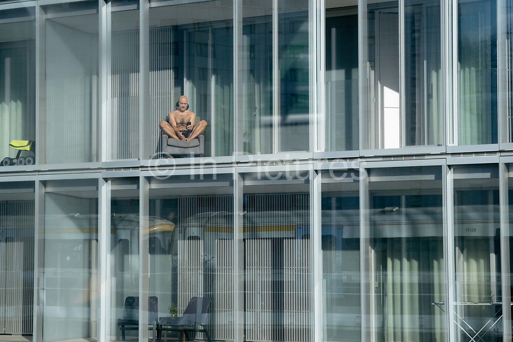 A man holding two phones sits sunbathing on a chair and in the window of an apartment block at the Battersea Power Station development, on 19th February 2021, in London, England.