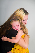 Mother comforts her crying daughter