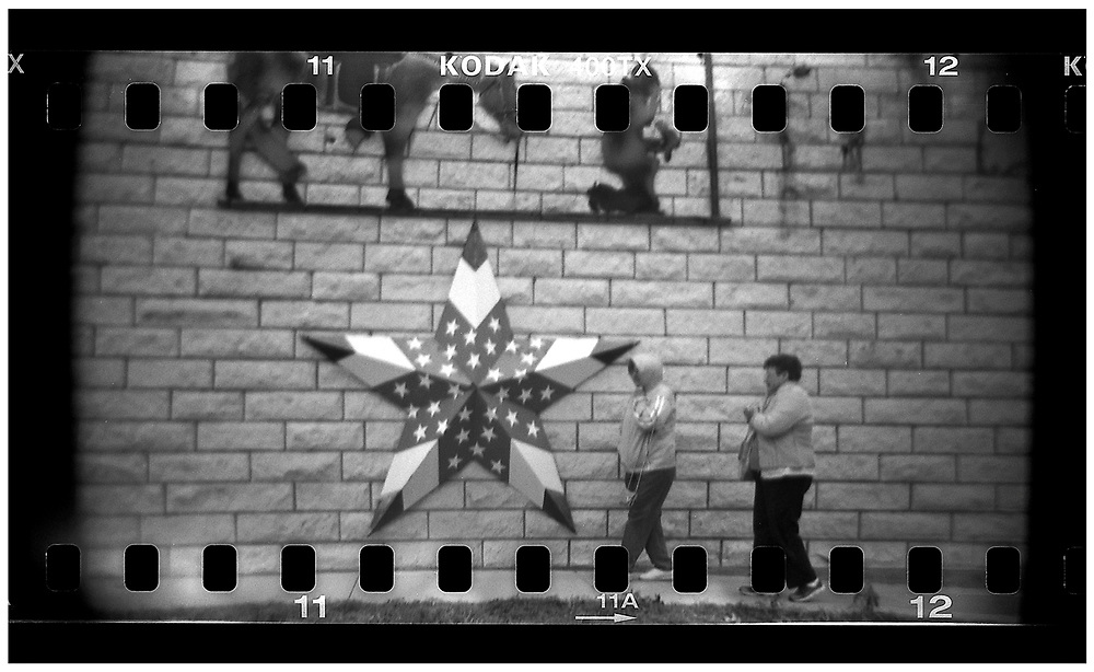 People walk past a wall with a star decorated with an American flag attached in Crawford, Texas, December 13, 2008. Bush moved to the small Texas town, population 705, in 1999 during his run for the presidency in 2000.The effect of the image was achieved by shooting 35mm black and white film in a medium format camera thereby exposing the entire negative including the sprocket holes of the film. REUTERS/Jim Young