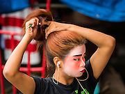 """14 MAY 2015 - BANGKOK, THAILAND:   A Chinese opera performer brushes out her hair before a show at the Pek Leng Keng Mangkorn Khiew Shrine in the Khlong Toey slum in Bangkok. Chinese opera was once very popular in Thailand, where it is called """"Ngiew."""" It is usually performed in the Teochew language. Millions of Chinese emigrated to Thailand (then Siam) in the 18th and 19th centuries and brought their culture with them. Recently the popularity of ngiew has faded as people turn to performances of opera on DVD or movies. There are still as many 30 Chinese opera troupes left in Bangkok and its environs. They are especially busy during Chinese New Year and Chinese holiday when they travel from Chinese temple to Chinese temple performing on stages they put up in streets near the temple, sometimes sleeping on hammocks they sling under their stage. Most of the Chinese operas from Bangkok travel to Malaysia for Ghost Month, leaving just a few to perform in Bangkok.       PHOTO BY JACK KURTZ"""