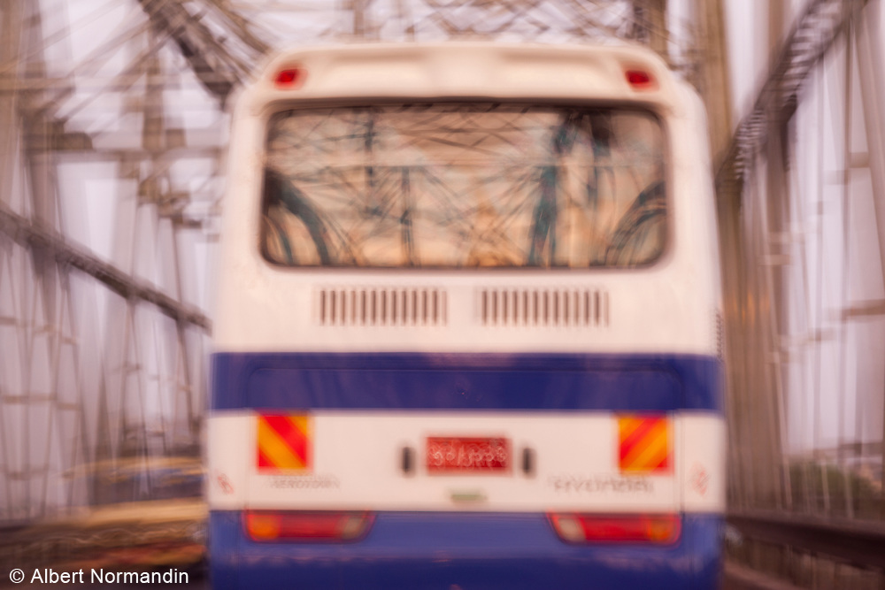 Bus in motion, crossing old bridge with reflections in windows. Baying Naung Bridge crossing Hlaing River