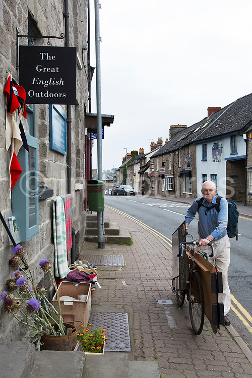 """Man pushes an awkward load on his bicycle in Hay-on-Wye or Y Gelli Gandryll in Welsh, known as """"the town of books"""", is a small town in Powys, Wales famous for it's many second hand and specialist bookshops, although the number has declined sharply in recent years, many becoming general antique shops and similar."""