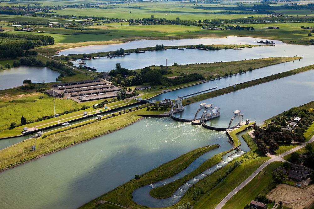 Nederland, Zuid-Holland, Hagestein, 12-06-2009; stuw in de rivier de Lek, dient om het waterpeil in de rivier te reguleren en het scheepvaartverkeer mogelijk te maken. Als gevolg van de geringe wateraanvoer is de vizierschuif gesloten, vissen kunnen gebruik maken van de de vistrap (of vispassage) onder in beeld, in het midden de schutsluis voor de scheepvaart. Op de landtong (links) een oude steenfabriek, nu stalling van caravans..Weir in the river Lek, regulates and manages the water level. The Lek is a rain river, with especially in the winter large amounts of water (melt water), in the summer there is a shortage of water, the weir ensures sufficiently high water level for shipping. Next to the dam fish ladder and shipping lock. .Swart collectie, luchtfoto (25 procent toeslag); Swart Collection, aerial photo (additional fee required); .foto Siebe Swart / photo Siebe Swart