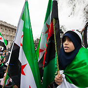 A young woman listens to the speeches in Whitehall holding a Syrian flag. An Anti-Assad Syrian demonstration held in Whitehall, Central London. The demonstration was called by the Syrian Community in the UK under the head lines; Syrians are being killed in a genocide and the world is watching. Several hundreds gathered opposite Downing Street 10 calling for Syrians to unite and the world to intervene.