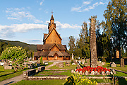 """A stone monolith and cemetery headstones rise at Heddal stave church, Norway's largest stave church. This triple nave stave church, which some call """"a Gothic cathedral in wood,"""" was built in the early 13th century and restored in 1849-1851 and the 1950s. Heddal stavkirke is in Notodden municipality, Telemark County, Norway."""