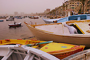 The port of Alexandria, Egypt during a sandstorm. The yellow-orange light is from the sand in the sky filtering the sunlight.