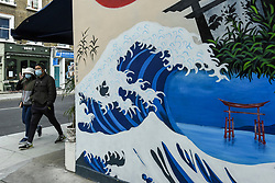 © Licensed to London News Pictures. 26/09/2020. LONDON, UK. A couple wearing facemasks pass a mural of the Hokusai's Great Wave in the West End of the capital.  As the number of coronavirus cases continues to rise heralding a second wave of the pandemic, it is reported that London may soon face more comprehensive lockdown restrictions.  Photo credit: Stephen Chung/LNP