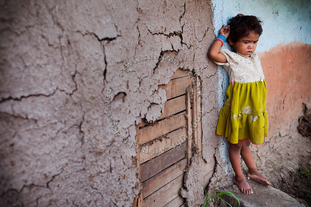 A young girl is standing near her home in the impoverished Oriya Basti colony in Bhopal, Madhya Pradesh, located near the former Union Carbide (now DOW Chemical) industrial complex.