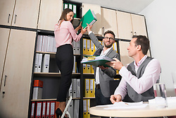Three young business colleagues working in office