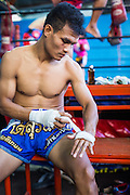 """18 DECEMBER 2104 - BANGKOK, THAILAND: A boxer wraps his hands before sparring at the Kanisorn gym in Thonburi. The Kanisorn boxing gym is a small gym along the Wong Wian Yai - Samut Sakhon train tracks. Young people from the nearby communities come to the gym to learn Thai boxing. Muay Thai (Muai Thai) is a Thai fighting sport that uses stand-up striking along with various clinching techniques. It is sometimes known as """"the art of eight limbs"""" because it is characterized by the combined use of fists, elbows, knees, shins, being associated with a good physical preparation that makes a full-contact fighter very efficient. Muay Thai became widespread internationally in the twentieth century, when practitioners defeated notable practitioners of other martial arts. A professional league is governed by the World Muay Thai Council. Muay Thai is frequently seen as a way out of poverty for young Thais and Muay Thai camps and schools are frequently crowded. Muay Thai professionals and champions are often celebrities in Thailand.     PHOTO BY JACK KURTZ"""