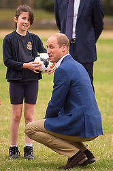 The Duke of Cambridge joins in football practice with children from the Wildcats Girls' football programme, during a reception for the England Women football team at Kensington Palace in London.