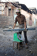 Color film photograph of a Vietnamese worker weighing a large metal bar in Da Hoi steel production craft village, Hanoi outskirts, Vietnam, Southeast Asia