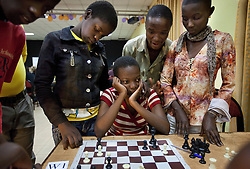 Peer watch Phiona Mutesi, a 14-year-old chess prodigy, play chess in Kampala, Uganda, Dec. 11, 2010. Mutesi lives in the slums of Uganda and is just now learning to read. But her instincts have made her a player to watch in international chess. Mutesi, a naturally talented chess player is coached by Robert Katende of Sports Outreach Ministry. The chess club meets at the Agape Church inside Katwe, the largest slum in Kampala.