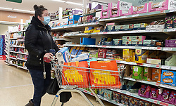 """© Licensed to London News Pictures. 22/12/2020. London, UK. A shopper in Sainsbury's supermarket in north London buying festive groceries and food items, just three days before Christmas day. A number of supermarkets have warned that some items may run low this week. Prime Minister Boris Johnson urged in a press conference for people to """"shop normally"""". It came after France closed the borders - banning UK travellers to their country, to stop the spread of the new variant of Covid-19. Photo credit: Dinendra Haria/LNP"""