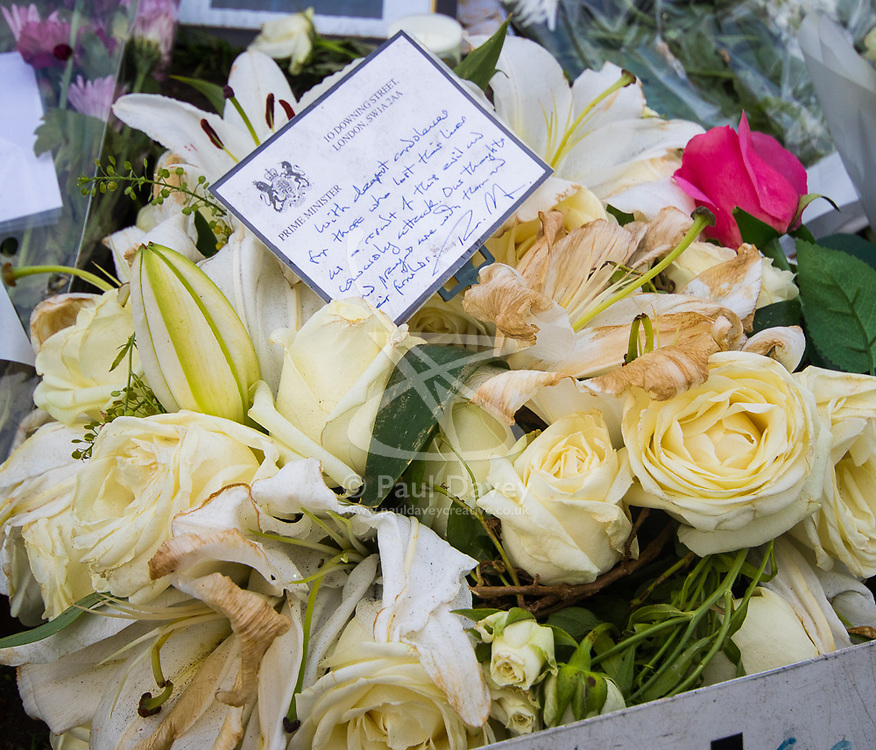 Westminster, London, March 27th 2017. Looking rather bedraggled, the Prime Minister Theresa May's formal tribute and handwritten card lies among the many hundreds in Parliament Square. Credit: ©Paul Davey<br /> <br /> ©Paul Davey<br /> FOR LICENCING CONTACT: Paul Davey +44 (0) 7966 016 296 paul@pauldaveycreative.co.uk