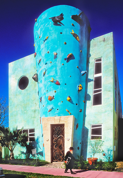 """An orthodox Jew strolls by a most unorthodox, postmodern, townhouse designed by Tod Tragash of STA Architectural Group. <br /> <br /> The building is named """"El Cyclone"""" after the cyclonic shape of its central stairwell.<br /> <br /> Decorating the exterior are playful, ceramic sea creatures by Miami sculptor Carlos Alves.<br /> <br /> And the front door is guarded by an octopus-shaped metal gate."""