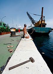 Un operaio sulla banchina del porto di Brindisi, sistema una grossa catena che servirà per far attraccare le barche a vela che gareggeranno. La grossa catena viene sistemata lungo tutta la banchina.