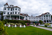 View of the Island House Inn from just off of Main Street, with tourists, Mackinac Island, Michigan, USA.