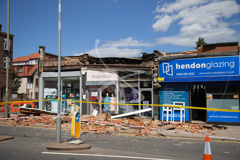 """A facade on a row of shops on Brent Street in Hendon has collapsed, causing police to close off the road whilst they make the site safe. No injuries were reported. According to the manager of the Hendon Glazing, Lucian Filote, 30, """"We were working in the shop as usual when we heard a loud bang. At first we thought it was a crash on the road but as we approached the shop entrance we saw the pile of rubble outside. Our first concern was that someone might have been hit by the falling bricks. We went and looked in the rubble but there was no one. We were concerned for our safety as there was a reinforcing bar with a lump of concrete hanging from it."""" . Hendon, London, June 18 2018."""