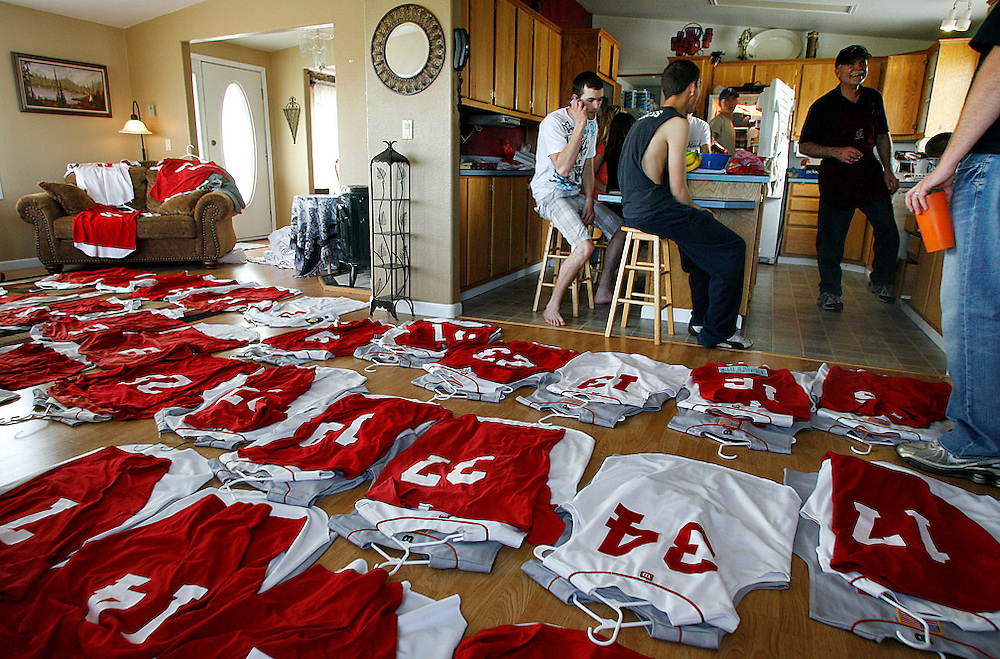 "The Burgesses prepare for a barbecue in the kitchen as uniforms for the Pasco Sun Devils American Legion baseball team fill the living room. Wayne, right, is the president of the board, and his wife Becky is the treasurerer. As the summer season approached, they had to take inventory and figure out which home and away jerseys needed replacing. Though Luke and Levi played for different teams during the high school season, Legion ball will give them one last time to play together. ""He'll probably be pitching, and I'll play outfield, backing him up when they hit bombs,"" says Levi. ""Thanks, Levi,"" says Luke. ""It'll be fun,"" says Levi. ""We go back to being brothers."" Luke, being a freshman on the senior team, will see limited playing time. ""I knew I wasn't going to play at all in Wenatchee,"" he says. ""When Levi told me I might not be able to play, I just asked him if I could be in the dugout, at least. It was fun to sit in the dugout with all the guys, and I was actually nervous."""