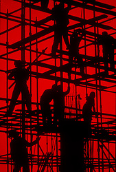 Stock photo of the silhouette of construction workers on a red background