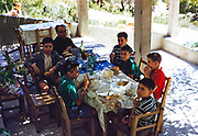 Group of boys eating sandwiches at shady cafe table accompanied by a man possibly a priest, island of Ibiza, Balearic Islands, Spain, 1950s
