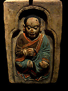 Monk seated holding a rosary and a sutra. first half of the 10th century. Tang dynasty (618-907 A.D). Brick, terracotta and polychrome. Chinese