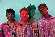 Young men covered in colourful paint powder during the festival of Holi in the city of Jaipur, Rajasthan, India.