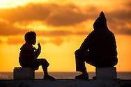 A boy and a man watching the sunset at the sea in Essaouira.