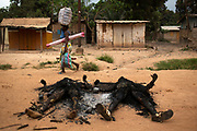 A woman passes charred bodies while fleeing with her belongings during one of the latest incidents of sectarian violence in the capital Bangui.