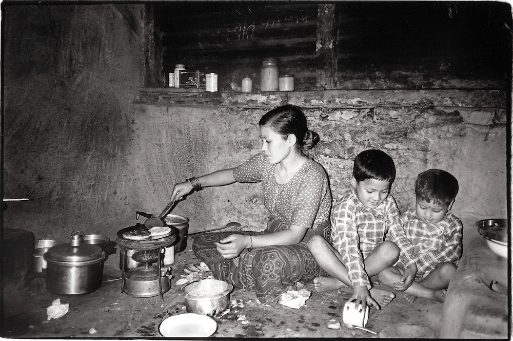 In a walk-up apartment in Kathmandu, a Nepali mother cooks dinner for her two sons on a one-burner kersosine stove. Toned black and white image. Editorial stock photo, not for advertising use, stock photography,