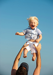 Little boy having fun being tossed in the air by a man