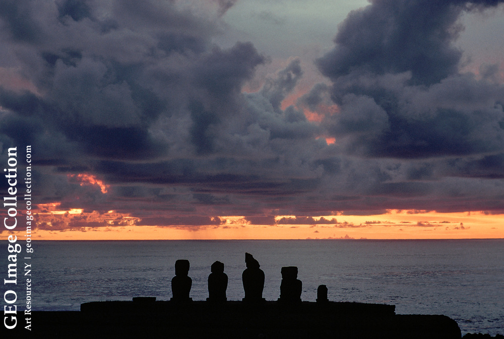 Moai carvings, silhouetted at sunset.