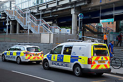 © Licensed to London News Pictures. 10/07/2020. London, UK. Police vehicles remain parked at a crime scene at Crossharbour DLR station in Poplar. Police were called shortly after 18:00hrs to reports of two males injured at Alexia Square, E14 close to Crossharbour DLR station. Officers attended and found a man, believed aged in his late teens or early 20s, suffering stab injuries. Emergency services provided first aid but despite their efforts, he was pronounced dead at the scene. A second male, believed aged in his late teens, was taken by the LAS to an east London hospital. Photo credit: George Cracknell Wright/LNP